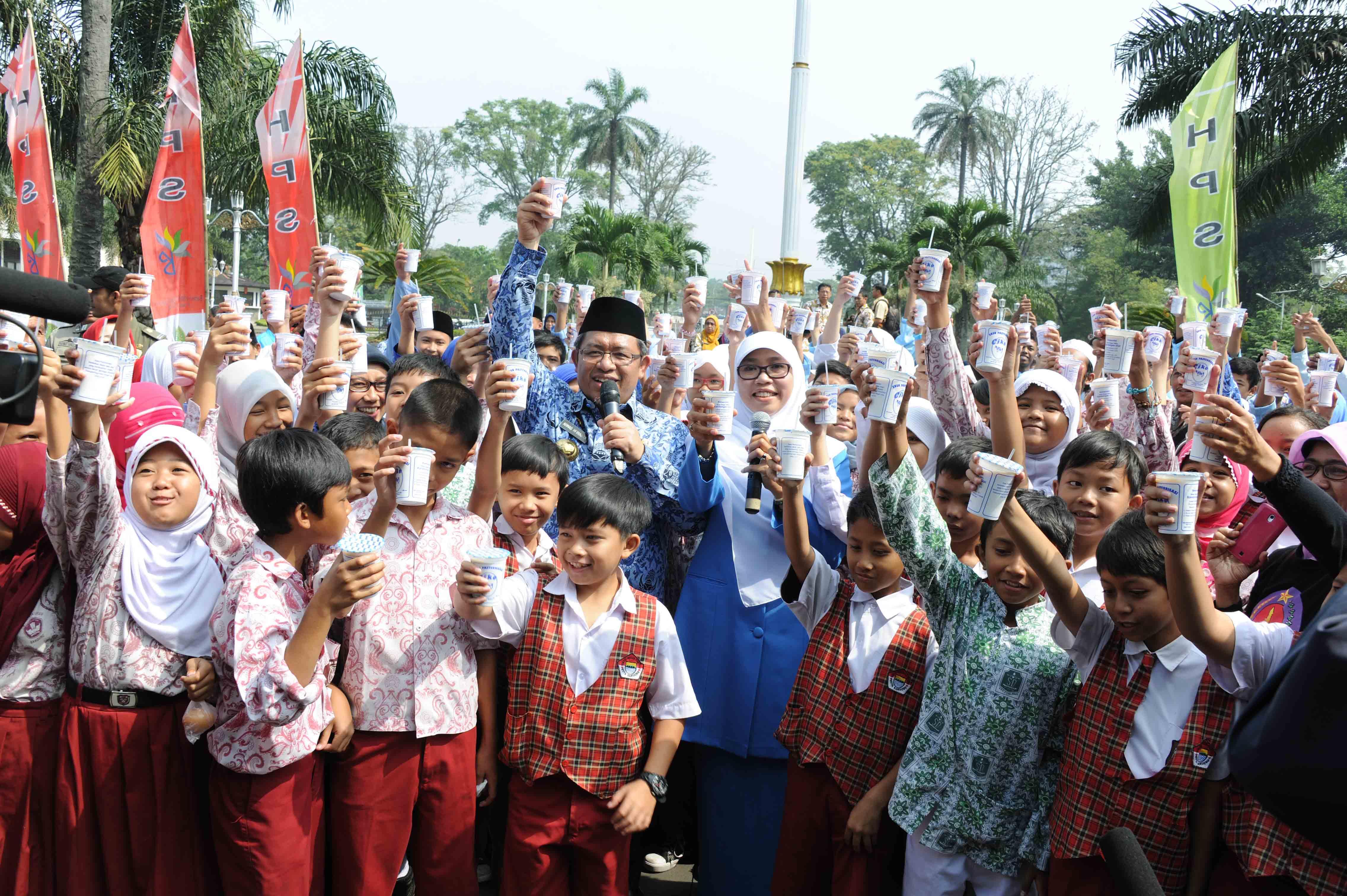 Gubernur Jabar Ahmad Heryawan didampingi Ibu Netty Heryawan minum susu dan makan telur ayam bersama puluhan anak SD di halaman Gedung Sate