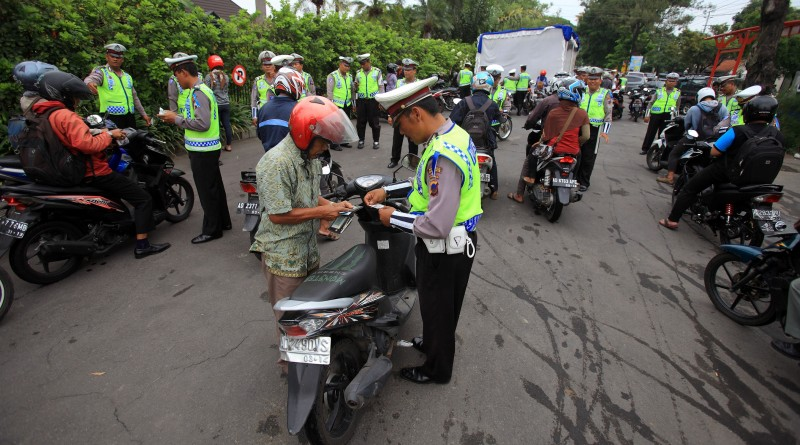 Polisi Laluintas memeriksa kelengkapan dan surat kendaraan bermotor pengendara saat Operasi Zebra Candi 2014 di Jalan Bhayangkara, Solo, Jawa Tengah, Senin (8/12). Operasi Zebra Candi 2014 yang digelar serentak se-Indonesia dari 26 November hingga 9 Desember 2014,  bertujuan untuk menyadarkan pengendara tentang pentingnya mentaati peraturan lalu lintas. ANTARA FOTO/Maulana Surya/ss/ama/14.