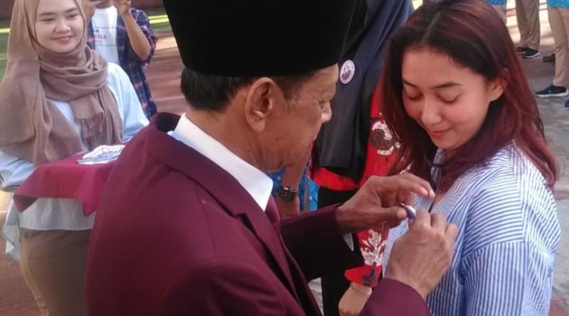 LEPAS: Rektor UKRI Dr Boyke Setiawan MM menyematkan pin kepada mahasiswa menandai pelepasan pengabdian mahasiswa di kampus UKRI Jalan Terusan Halimun Bandung